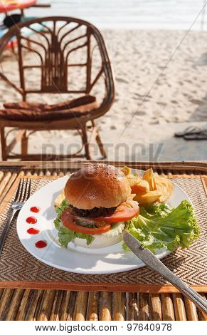 Hamburger And French Fries In Beach Cafe