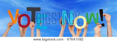People Hands Holding Colorful Word Vote Now Blue Sky
