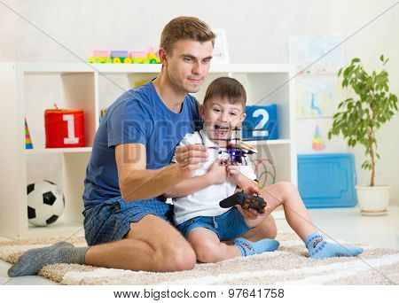 Dad and his son child play with RC helicopter toy