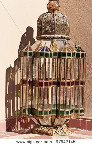 Old Arabic multi coloured glass lamp standing against a wall in a Moroccan market in full sun