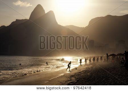 Brazilian Ipanema beach Rio de Janeiro at sunset silhouettes flare