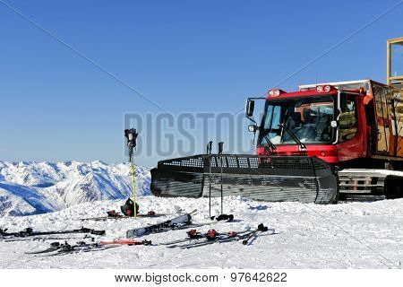 Snow plough used for snow grooming standing on top of Alps mountains