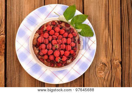 Homemade Round Chocolate Cake With Fresh Wild Raspberries And Green Leaves In Blue Checkered Plate O