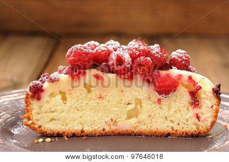 Homemade Sponge Cake With Fresh Juicy Wild Raspberries And Icing Sugar Cut In Halves In Brown Plate