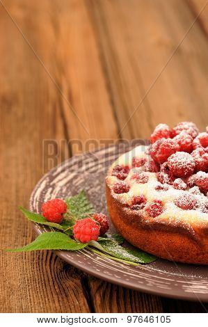 Homemade Yummy Cake With Fresh Wild Raspberries And Leaves Decorated With Icing Sugar In Brown Plate
