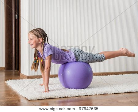 smiling girl with african braids on the ball for fittnes at home