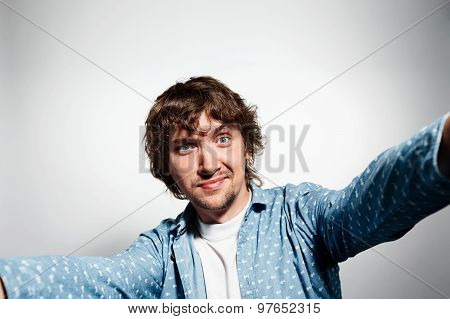 Close Up Portrait Of A Young Attractive Man Holding A Smartphone Digital Camera With His Hands And T