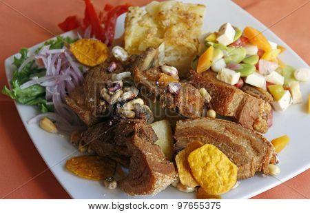 Peruvian food, Chicharron (fried pork) with potatoes, onion garnish, canchita.