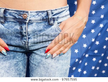Young woman with marine sailor gel nails manicure holding hand at jeans  pocket