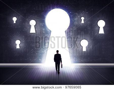 Successful businessman looking through keyhole