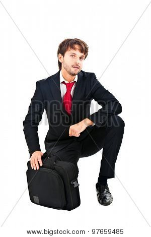 Successful young businessman kneeling full length