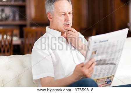 Mature man reading a newspaper in his living room