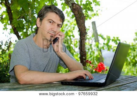 young man at the phone and tablet pc, outdoor