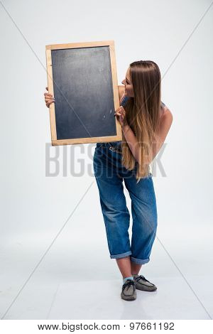 Full length portrait of a female student holding blank board and looking on it isolated on a white background