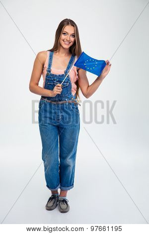 Full length portrait of a happy woman holding european union flag isolated on a white background. Looking at camera