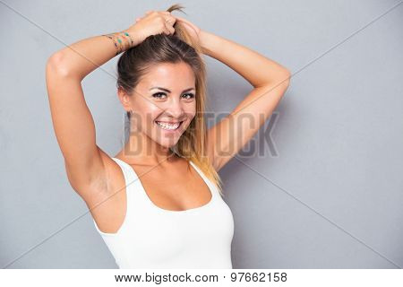Portrait of a cheerful young woman holding her ponytail over gray background