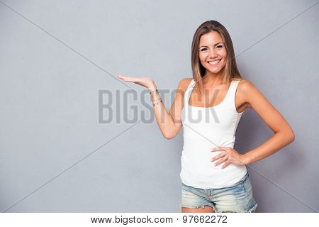 Happy cute girl holding copyspace on the palm over gray background