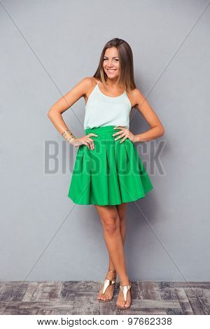 Full length portrait of a smiling pretty woman standing on gray background. Looking at camera