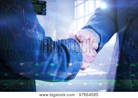 Business people shaking hands close up against stocks and shares