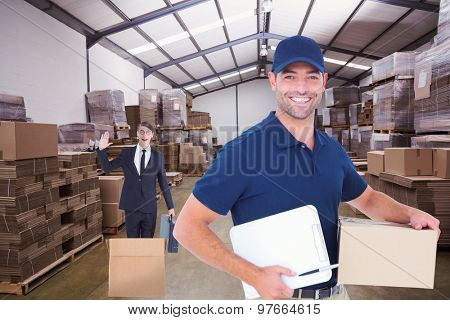 Happy delivery man with cardboard box and clipboard against forklift in a large warehouse