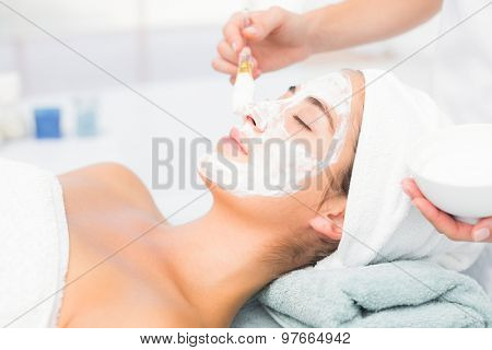 Side view of an attractive young woman receiving treatment at spa center
