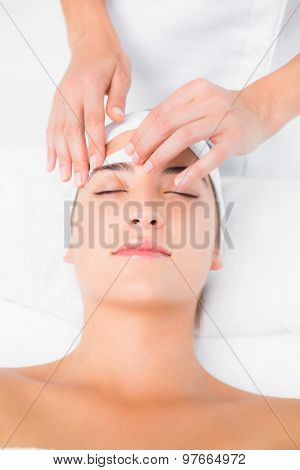 Close up of a hand waxing beautiful womans eyebrow