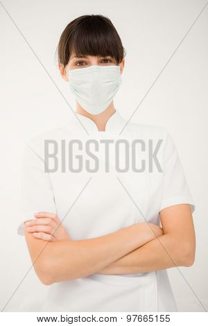 Nurse wearing protective mask with arms crossed on white background