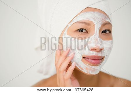 Portrait of an attractive woman with cream treatment gesturing at the health spa