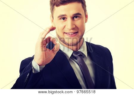 Handsome businessman showing perfect sign.