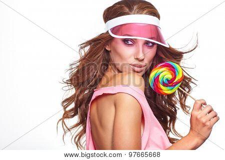 Bright makeup. Beauty Girl Portrait holding Colorful lollipop. Pink cap.