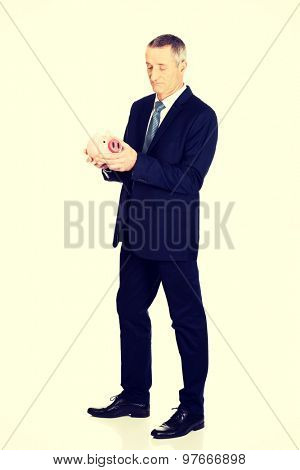 Full length confused businessman holding piggybank.