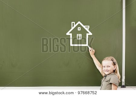 Cute girl of school age writing with chalk on blackboard