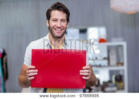 Portrait of smiling man holding up red blank sign in clothing store