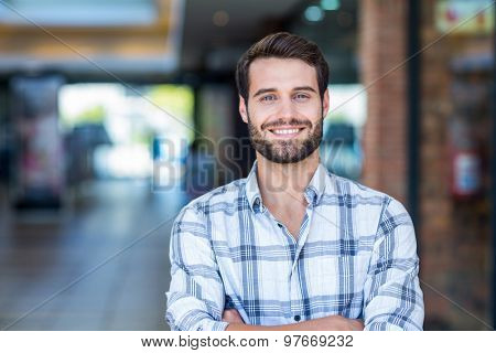 Portrait of man with arms crossed looking at camera at the mall