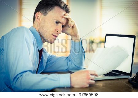 Focused businessman reading document at desk in his office