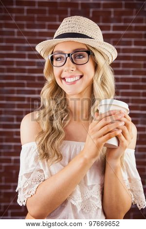 Gorgeous smiling blonde hipster holding take-away cup against red brick background
