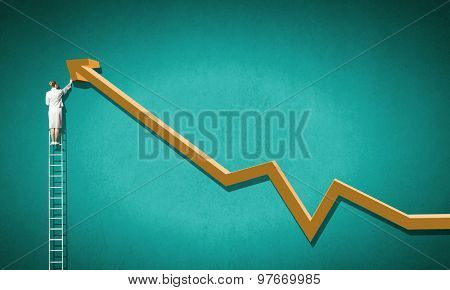 Rear view of businesswoman standing on ladder and drawing graph