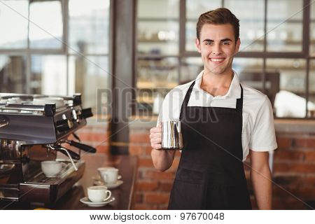 Portrait of smiling barista holding jug with milk at coffee shop