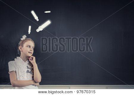 Cute thoughtful girl of school age standing near blackboard