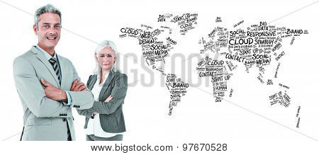 Smiling businesswoman and man with arms crossed against world map of buzzwords