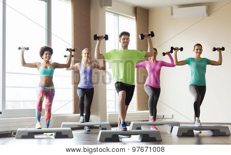 fitness, sport, aerobics and people concept - group of smiling people working out with dumbbells flexing muscles on step platforms in gym