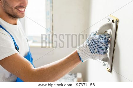building, profession and people concept - close up of smiling male builder sanding wall indoors