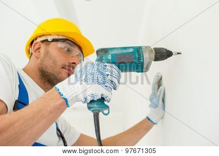 building, working equipment and people concept - close up of builder in hardhat perforating wall with drill indoors