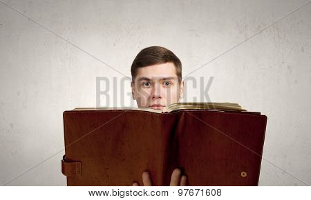 Young man with opened book in hands