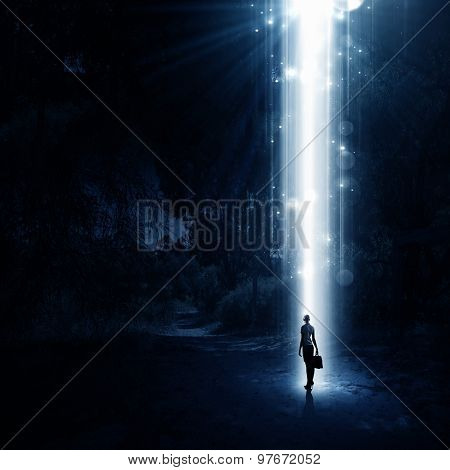 Rear view of businesswoman standing in light of way