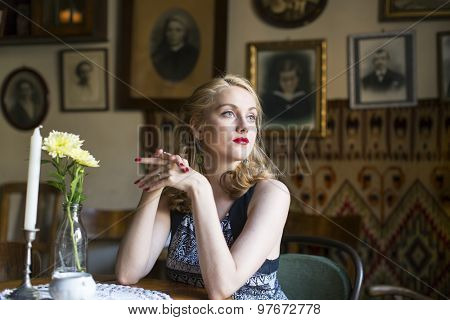 Young beautiful retro woman sitting at a table.