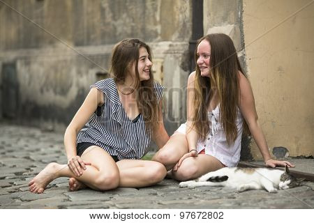 Happy girlfriends teenage girls sitting on the pavement with a cat.