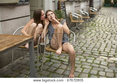 Girlfriends teenage girls gossiping while sitting in a street cafe.