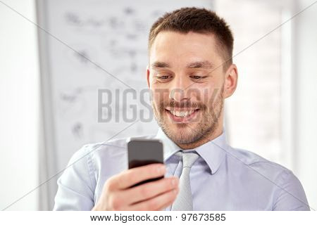 business, technology, internet and communication concept - young smiling businessman texting message on smartphone