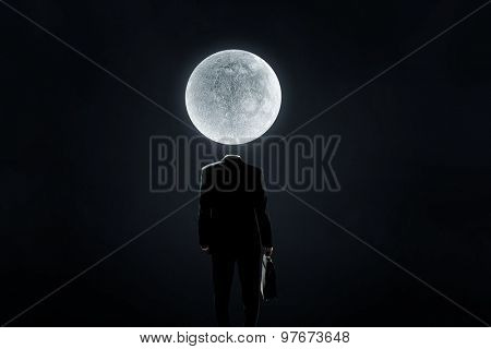 Faceless businessman with moon planet instead of head